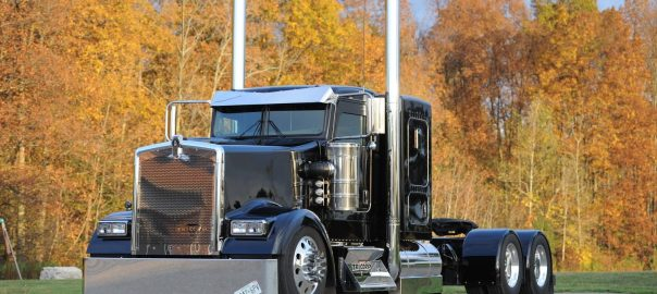 A photo of a black heavy truck in front of autumn foliage, for marketing the 2018 Wowtrucks calendar